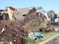 A Bobcat E50 compact excavator clears debris from a Moore, Oklahoma neighborhood after a 2013 tornado