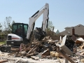 A Bobcat E50 compact excavator reaches for debris at the site of a Moore, Oklahoma home destroyed by a 2013 tornado