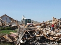A Bobcat E50 compact excavator clear debris from the site of a home in Moore, Oklahoma after it was destroyed by a 2013 tornado