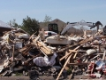 A Bobcat E50 compact excavator is surrounded by debris on the plot of a Moore, Oklahoma home destroyed by a 2013 tornado