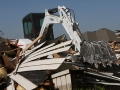 A Bobcat E50 compact excavator moves debris to the street of a Moore, Oklahoma neighborhood struck by a 2013 tornado