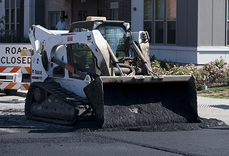 A Bobcat compact track loader dumps asphalt onto the road.