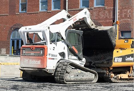 A Bobcat compact track loader dumps asphalt into a paver.