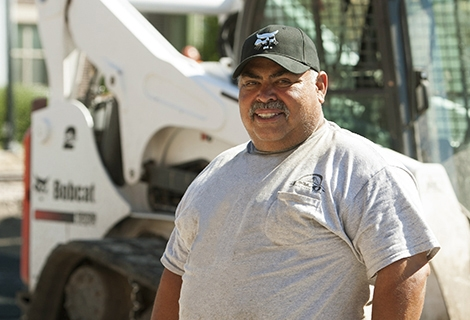 Gustavo Villarreal stands next to his Bobcat compact track loader.