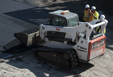 A Bobcat compact track loader holds a bucket full of asphalt next to the jobsite. Two construction workers stand nearby.
