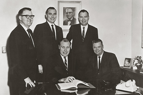 Following the death of E.G. Melroe in 1955, his sons and son-in-law took the reins at the Melroe Manufacturing Company. Seated are Clifford Melroe and Lester Melroe. Standing are Eugene Dahl, Irving Melroe, and Roger Melroe.
