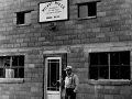 E.G. Melroe stands in front of Melroe Manufacturing Company building in 1948