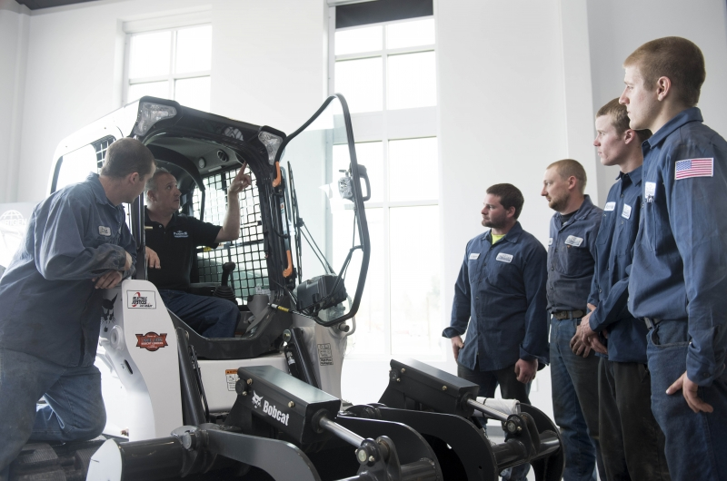 Service technicians gather around a Bobcat compact track loader inside Finke Equipment's learning center