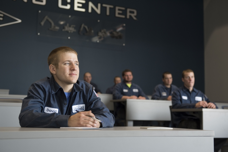 Finke Equipment service technicians take notes during a class while seated at desks inside the learning center