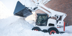 A Bobcat loader clears snow.