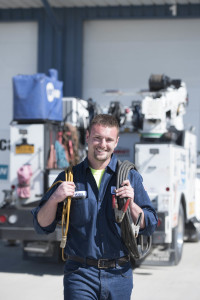Alex Giebitz poses in front of his mobile service truck with cables looped over his shoulders