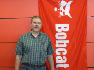 Bob Rowe stands next to an orange Bobcat banner