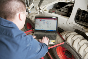 A service technician looks up diagnostics on his laptop next to a Bobcat skid-steer loader