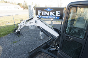 A Bobcat compact excavator sits beside a Finke Equipment sign alongside Finke's driveway