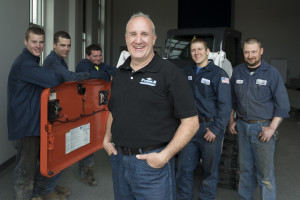 Steve Micelli and five service technicians stand beside a Bobcat compact track loader