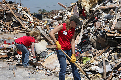 Volunteers clear debris in the streets of a Moore, Oklahoma neighborhood struck by a 2013 tornado
