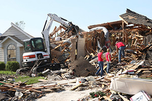 Volunteers and a Bobcat E50 compact excavator clear debris from the site of a home in Moore, Oklahoma destroyed by a 2013 tornado