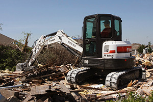 A Bobcat E50 compact excavator helps clear what remains of Gregg Thompson's home, which was destroyed by a tornado