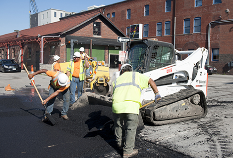 Construction workers load asphalt into a Bobcat compact track loader's bucket