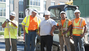 Gustavo Villarreal stands with four of his workers next to his Bobcat compact track loader