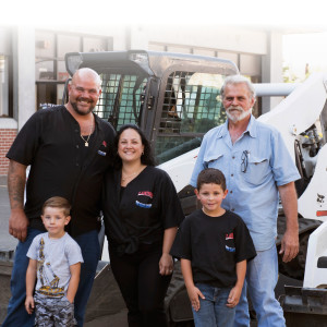 Ernie III stands alongside a Bobcat loader with his wife, Amy; sons Ernie IV and Tucker; and father, Ernie Jr.