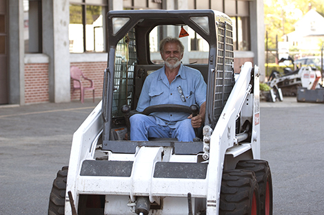 Ernie Jr. sits behind the wheel of a Bobcat skid-steer loader outside the Landry Rental Center store.