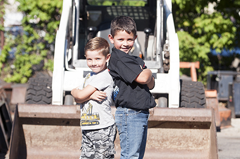 Tucker and Ernie IV pose in front of a skid-steer loader outside the Landry Rental Center store.