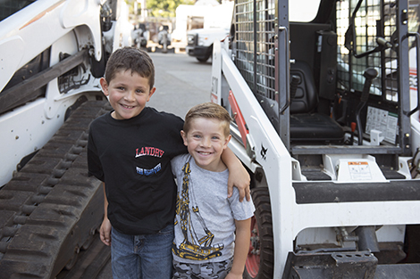 Ernie IV and Tucker place their arms around each other standing next to a Bobcat track loader and a skid-steer loader.