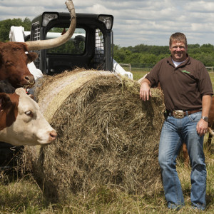 Todd Pugh leans against a hay bale with his cattle and Bobcat T650 loader in the background.