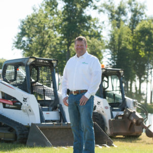 Todd Pugh stands next to two Bobcat loaders.