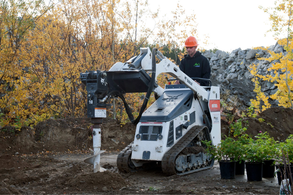 A photo of Matt operating an MT85 with auger attachment to create a hole for planing a tree on a jobsite.