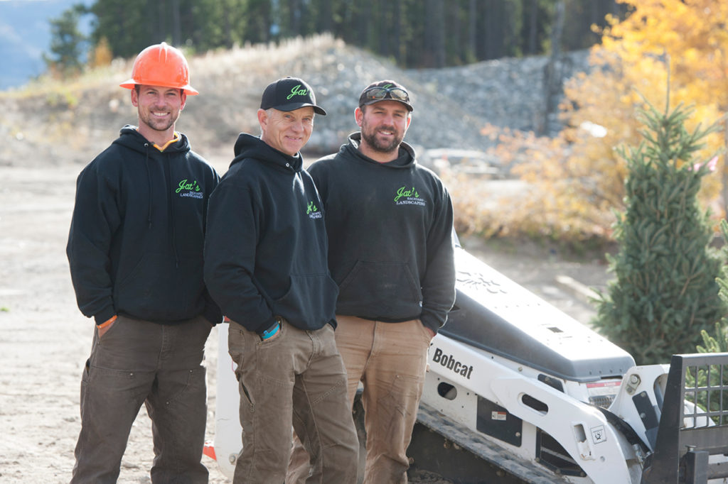 Matt, Alan and Nathan Thomson next to their MT85 mini track loader on a jobsite.