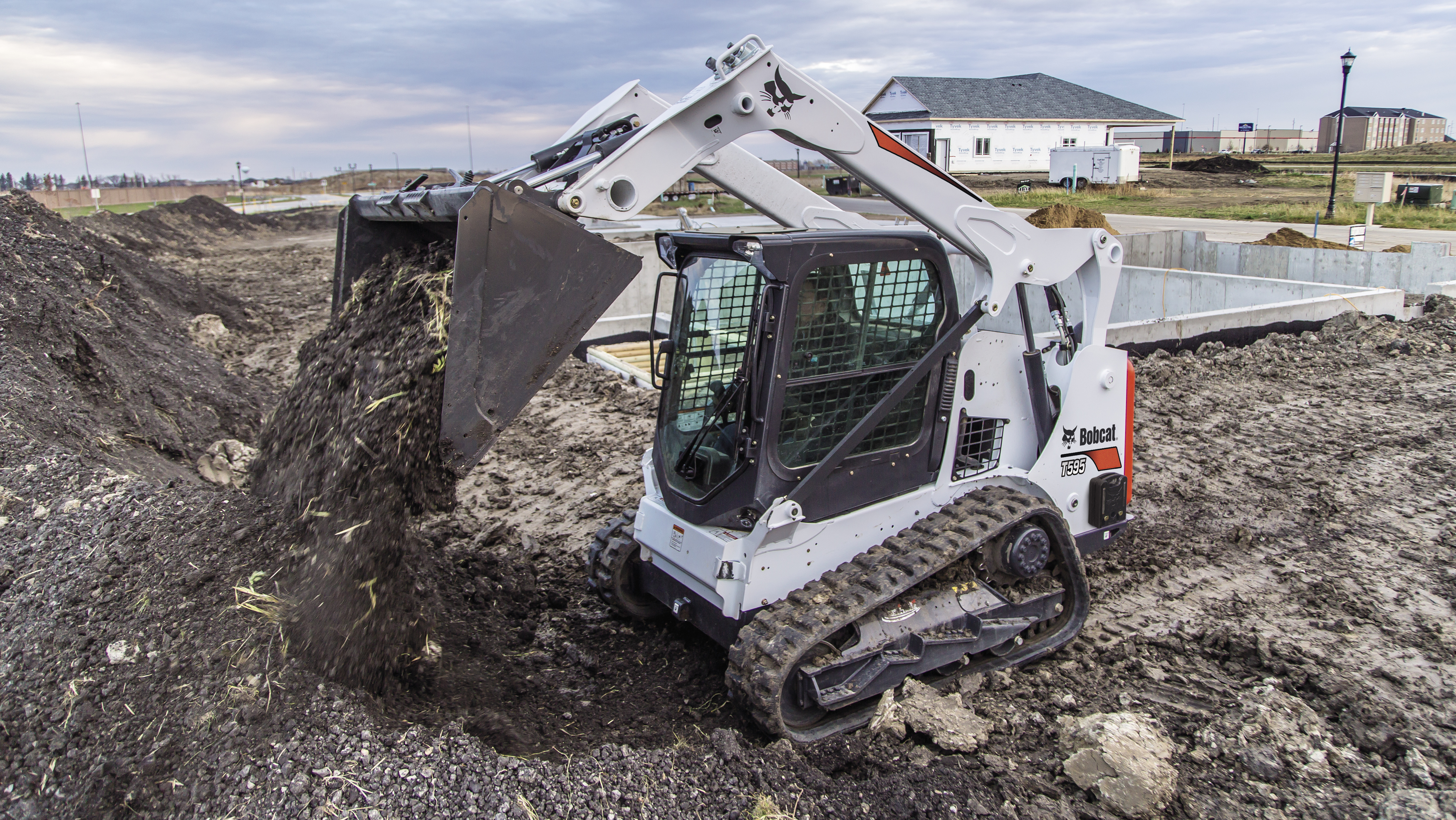 Bobcat T595 compact track loader dumping dirt on construction site