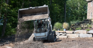 Bobcat T650 dumping dirt on a landscaping project
