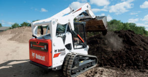 Bobcat T650 compact track loader dumps dirt
