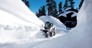 Bobcat skid-steer loader uses snowblower to remove snow from a driveway.