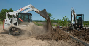 A Bobcat T590 compact track loader and an E35 excavator work at a construction site.
