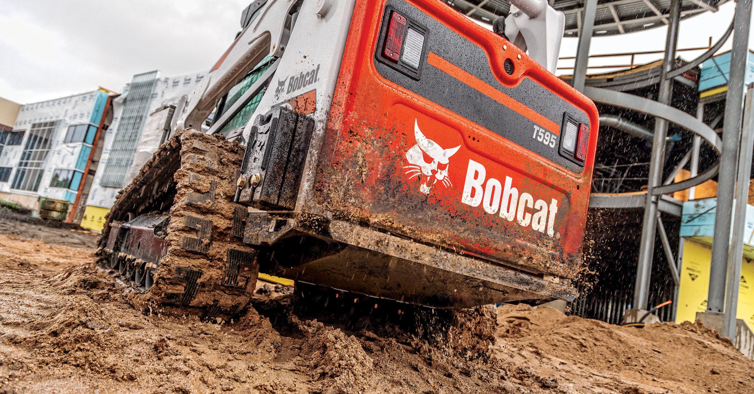 Bobcat T595 compact track loader powers through mud and stays productive on a busy construction site.