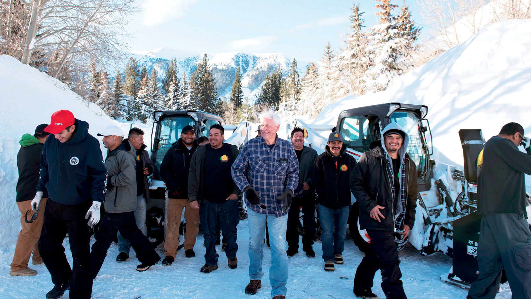 John Eastman stands with his snow removal crew next to skid-steer loader fleet.