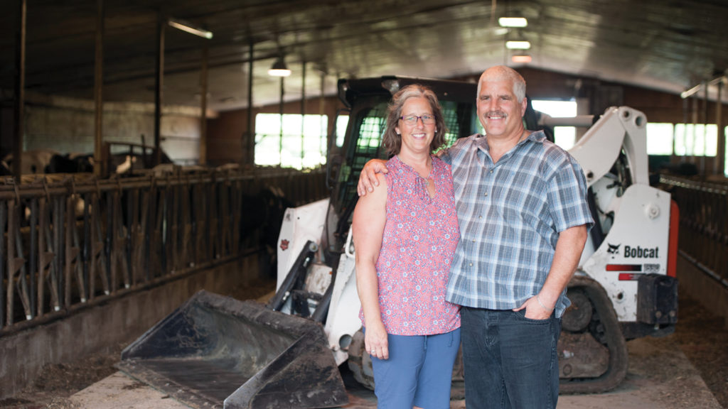 Karen and Les deLeeuw stand next to their Bobcat T590 compact track loader in their dairy barn
