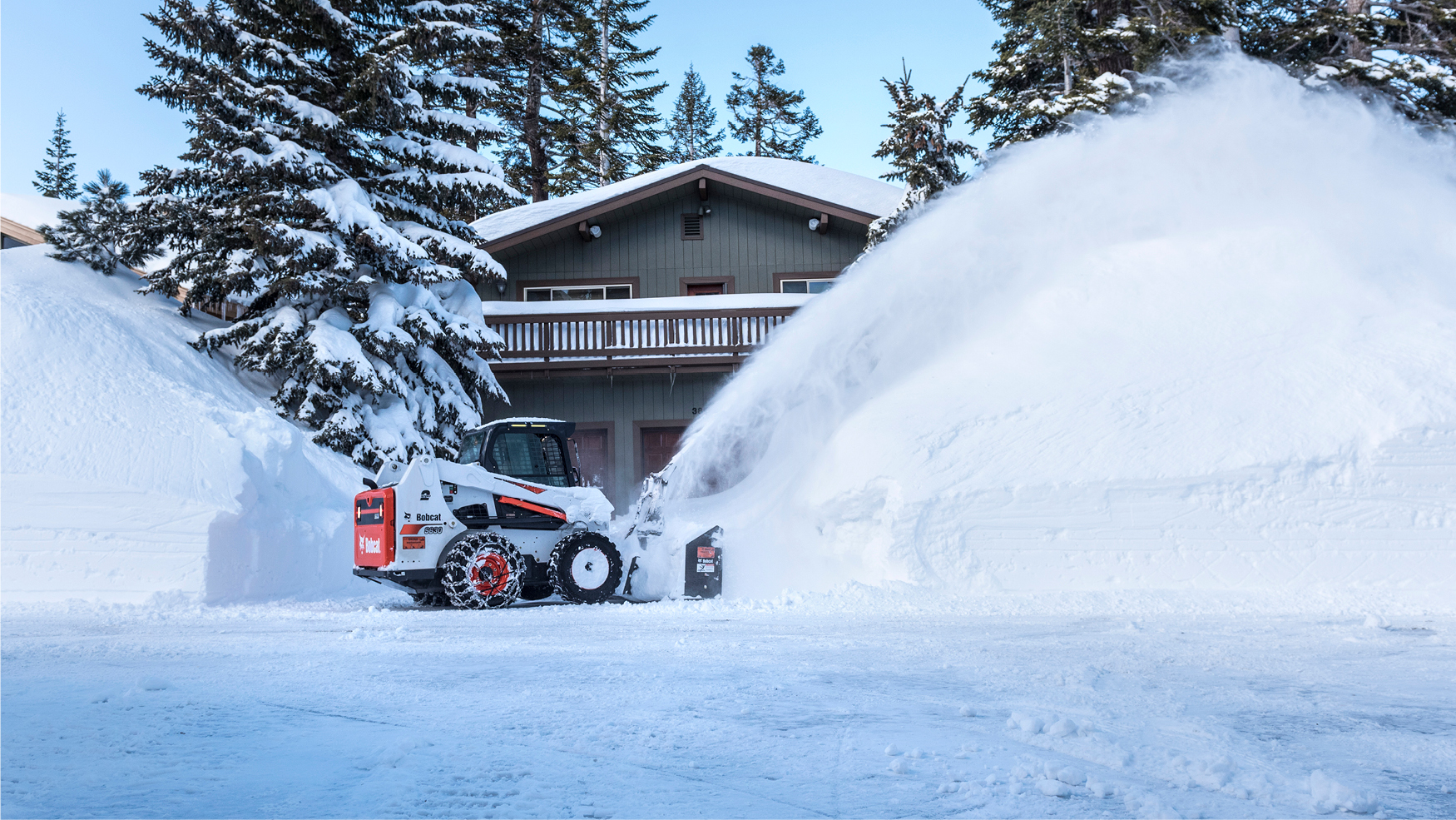 S630 clearing snow from a residence using a snowblower
