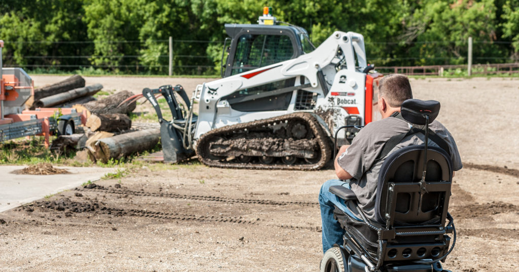 Sitting in his wheelchair, Trevor uses the Bobcat radio remote control system to pick up logs with his T595 compact track loader and grapple attachment.