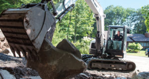 Landscaper moves rocks with his Bobcat excavator in the landscaping bed of his customer.