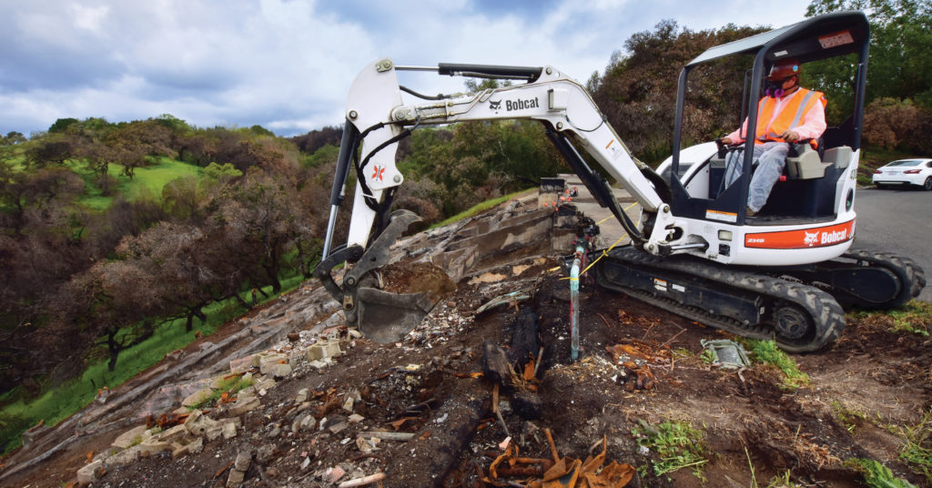 JM Environmental operator uses a 430 excavator to move debris from a wildfire site.