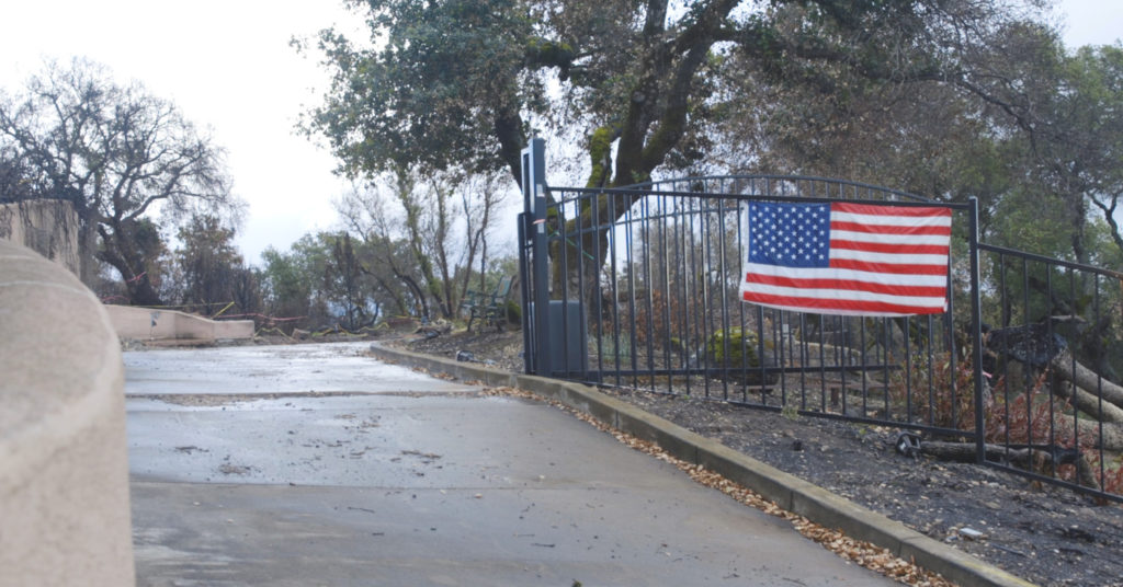 A former Santa Rosa home displays the American flag on their front gate.