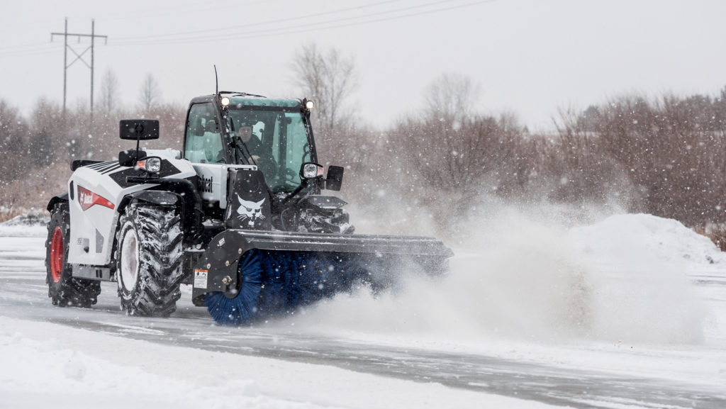 A Bobcat V519 VersaHANDLER® telescopic tool carrier equipped with an angle broom clears snow from a parking lot.
