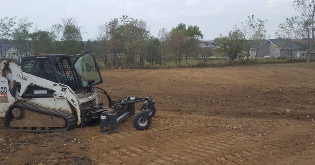 Chris Wagner's T190 with a soil conditioner attachment on a dirt jobsite.