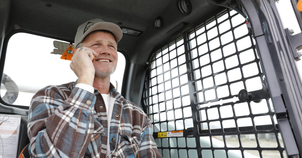 Todd Sharp talks on the phone in the cab of his Bobcat T650 compact track loader.
