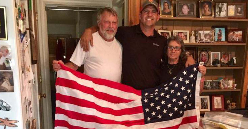 Three people hold an American flag saved in a California wildfire