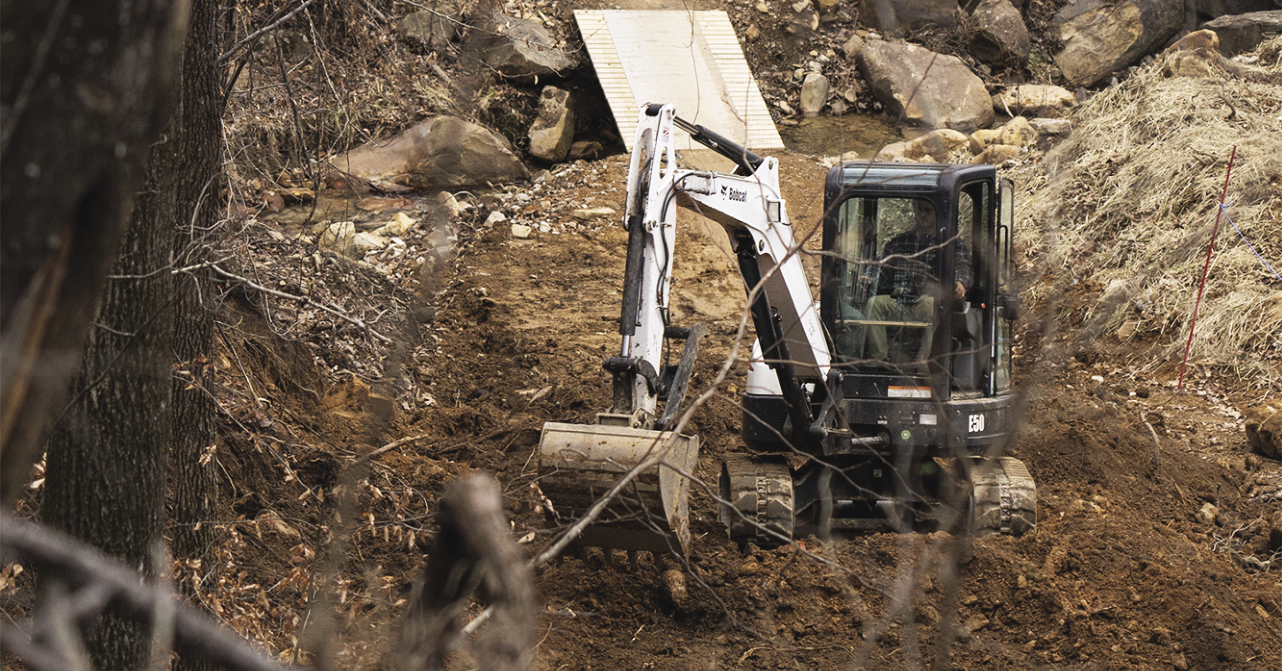 Bobcat E50 excavator digging a new trail at Windrock Bike Park.